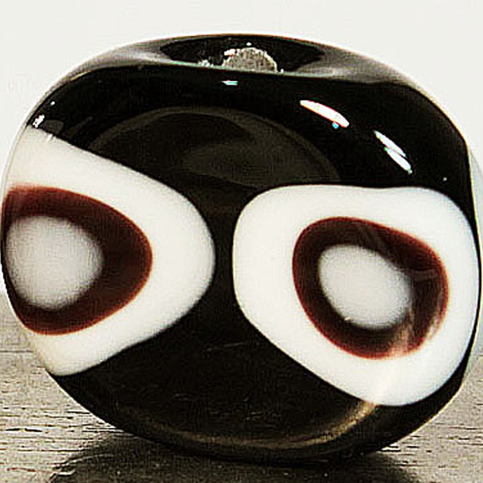 ovalada negra con varios lunares blancos y negros superpuestos