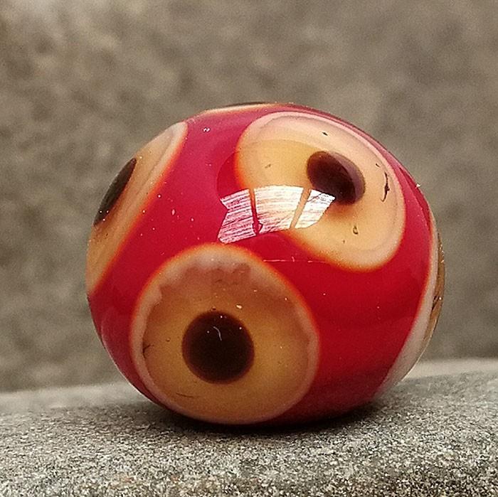 rojo claro con punto marfil, punto ámbar y punto negro superpuestos